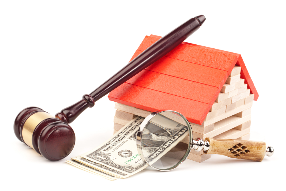 An auctioneer's gavel leaning against a model log house that has dollar bills coming out of the side of it, with a magnifying glass in front